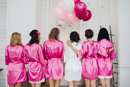 Bridesmaids in pink silk robes with the word bridesmaid on bac 스톡 콘텐츠