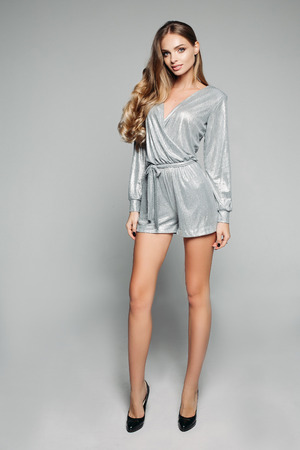 Beauty girl in fashionable silver overall and heels.