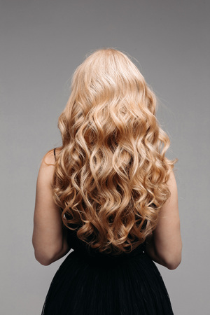 Beautiful female curly blond hairs - back view