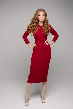 Splendida giovane donna in elegante abito da sera rosso e tacchi beige.