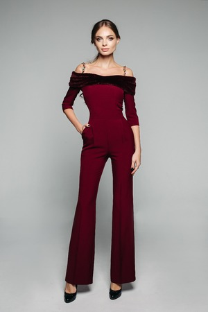 Elegant woman in bordo overall with bare shoulders and high heels.