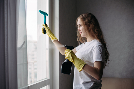 Side view of curly girl wearing protective gloves cleaning window. Banque d'images