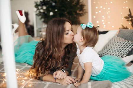 Mother kissing daughter. Concept of family, motherhood.