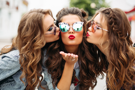 Gorgeous teenagers in sunglasses kissing their friend smiling at camera with heart gesture.