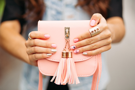 Beautiful womens hands with trendy manicure holding lovely peach crossbag.