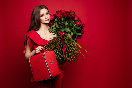 Girl with big bouquet of red roses on shoulder dreaming. Stock Photo