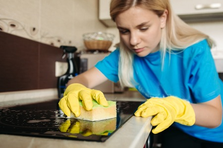 Woman, wearing in protective glove with rag, cleaning electric stove at home. Banque d'images