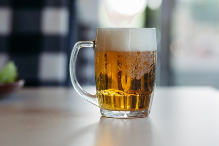 Horizontal photo of glass cup full of light fresh beer. 写真素材