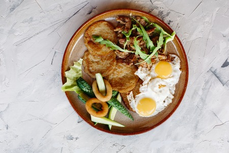 Delicious potato puncakes served with fried eggs.