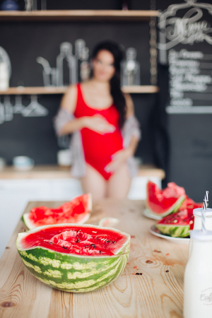 Halved bright watermelon on wooden table against unfocused pregnant woman. Imagens