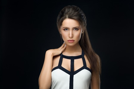 Brunette woman in stylish dress seductive looking at camera.