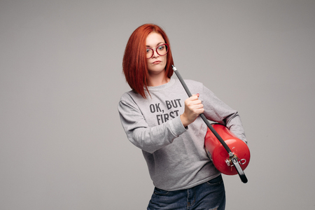 A woman with red hair in the Studio holding a fire extinguisher. An emotional bright woman extinguishes everything with a fire extinguisher. Фото со стока