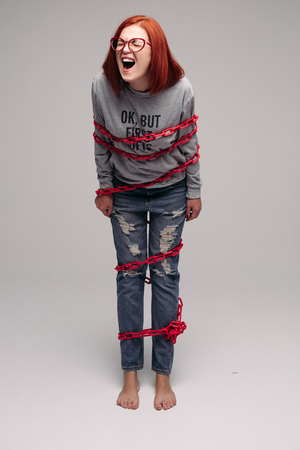 girl entangled in a chain,A red-haired woman with brown hair tries to get rid of the chain