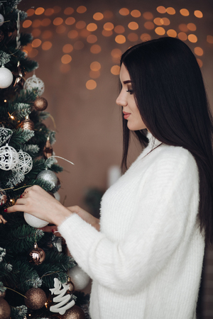 Beautiful woman with long dark hair in white sweater holds Christmas gift. 写真素材