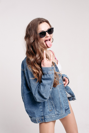 Funky girl in stylish sunglasses and denim jacket shows rock sign with hand.