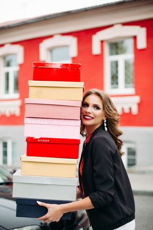 Stunning lady with stack of shoe boxes. Stock Photo