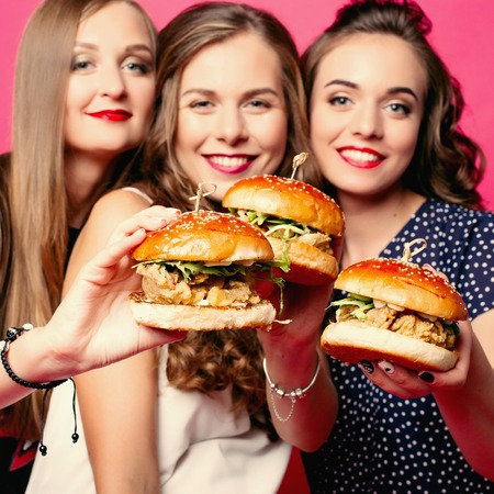 Pretty girlfriends with juicy hamburgers. Stock Photo