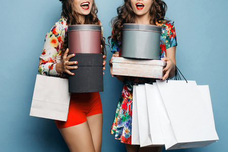 Smiling girlfriends in colorful clothes with many bags after shopping.