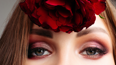 Pretty brunette lady with bright make up holding roses.