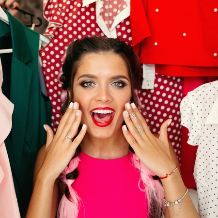 Frustreted brunette in pink having a problem of choosing clothes. Stockfoto