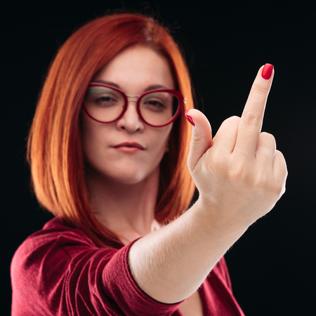 Confident and angry red haired girl showing finger, gesturing off.