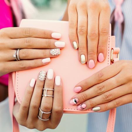 Chiuda in su della borsa con le mani di ragazze con manicure su di esso. Archivio Fotografico