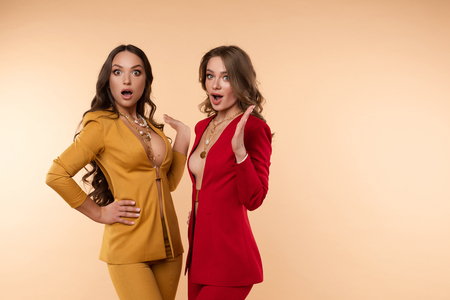 Two surprised women in jackets over bodies.