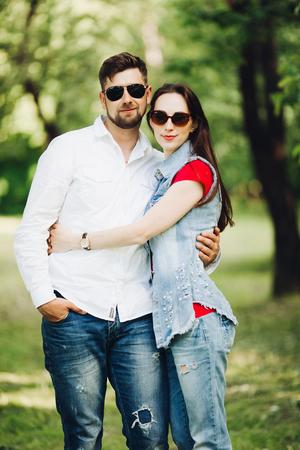 Porträt des jungen glücklichen Paares in der Liebe, lächelnd und im Garten umarmend.