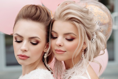 Two gorgeous models with make up and hairdo in white.
