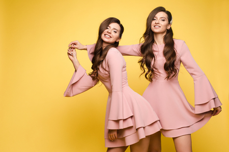 Happy sisters in pink dresses smiling and standing together. Reklamní fotografie