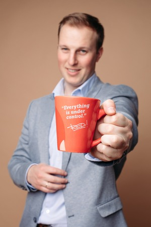 Successful businessman with cup with reassuring slogan. Фото со стока
