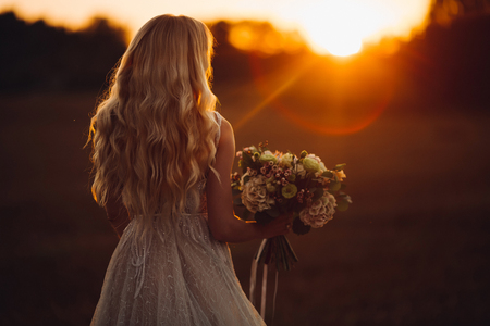 Unrecognazible blondy bride looking away and holding wedding boquet at sunset. Stock Photo