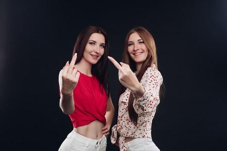 Twee jonge meisjes in casual kleding gebaren met de vingers.