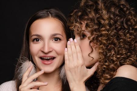 Shocked brunette posing while friend whispering secret