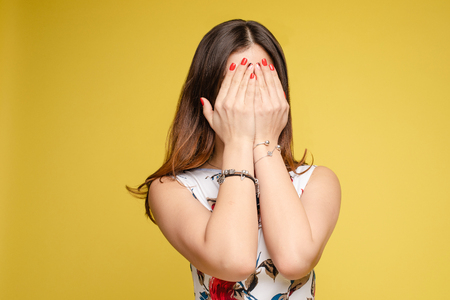 Amazed lovely woman covering face with hand Imagens