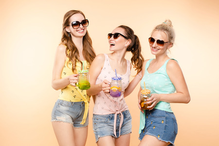 Three sporty girls drinking fresh juice and posing