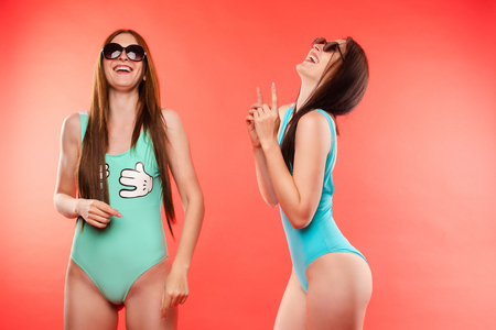 Young models in swimming wear together Concept of fit and body.