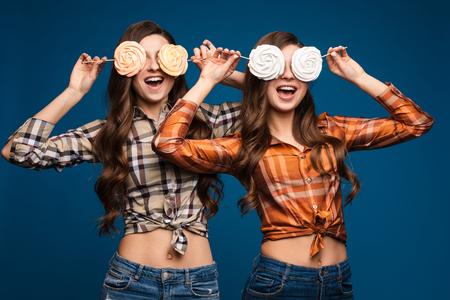 Happy girlfriends posing with sweet candies like rabbit ears. Stock Photo