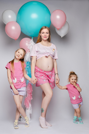 Funny photo of gorgeous pregnant mother with two daughters looking at their bellies.