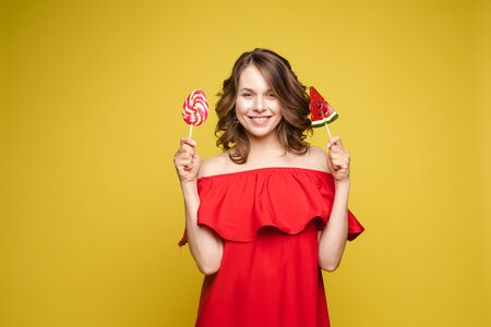 Fashionable young woman with lolipop in her hands on background Reklamní fotografie