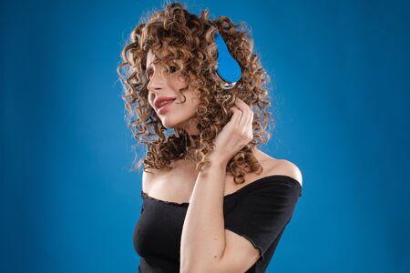 Woman in headphones listening music and dancing