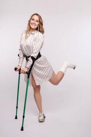 Happy woman with broken leg in bandage standing on crutches Stockfoto
