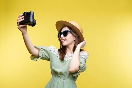Pretty girl in hat and summer dress taking selfie on camera.