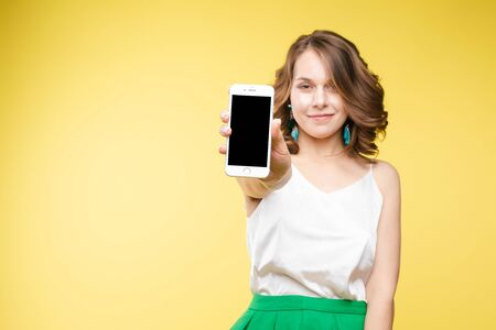 Girl showing mobile to the camera with shocked expression.