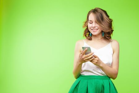 Pretty girl pointing at cell phone.Studio portrait of beautiful caucasian