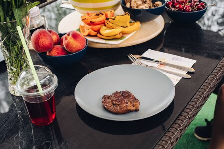 Table with appetizing fresh food barbeque meat on plate and fresh grilled vegetable fruit beverage