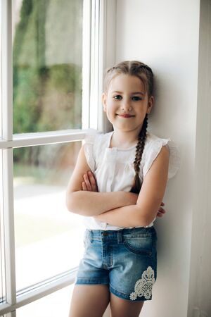 Adorable child with braid holding arms crossed on chest.