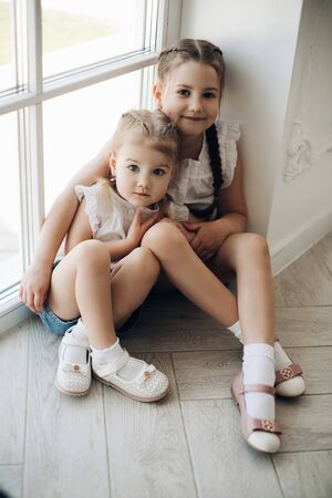 Two sisters sitting near window and hugging each other
