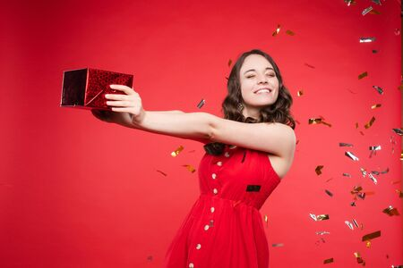 Gorgeous brunette girl in red dress in confetti. Stock fotó