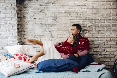 Couple in red Christmas jumpers kissing surrounded by pillows.